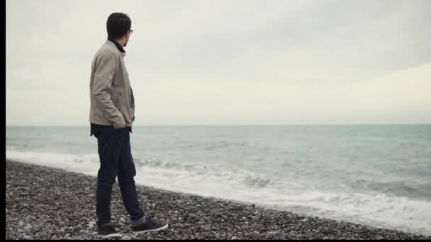Osamělý pohledný muž stojící na oblázkové pláži a při pohledu na moře