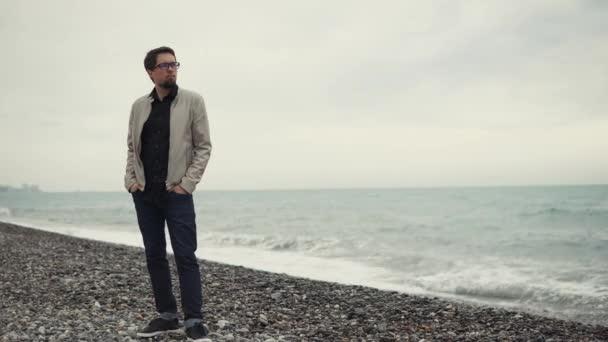 muž v brýlích se nachází na kamenité pláži u moře a dívá se jinam