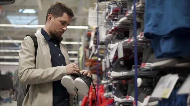 2a211e09b Cliente masculino está observando o par de tênis em uma área de vendas no  esporte armazenar– gráficos de vetor