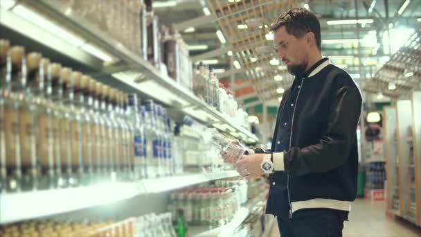 Dospělý člověk je stále láhve s vodkou z regálu obchodu s alkoholem