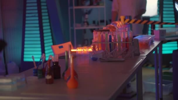 Table in secret chemical laboratory, vials with different colors liquids