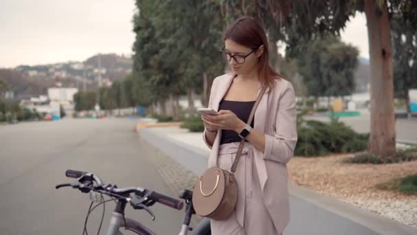 Okouzlující dívka čte a posílá vzkazy, stojící venku ve městě