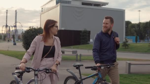 Man and woman talking on a walk rolling bicycles.