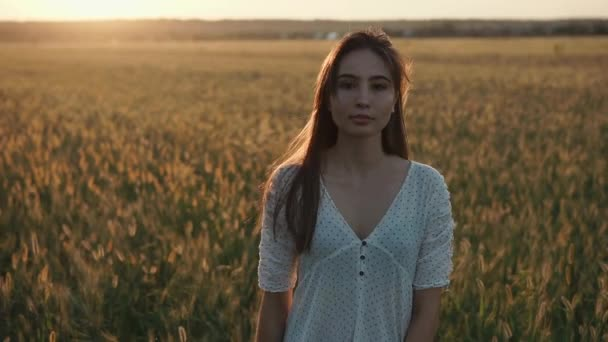 Thoughtful pretty girl is walking over field with wheat, sunset is in background