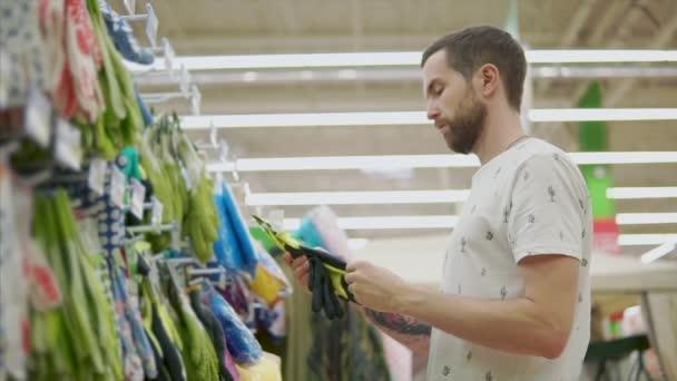Male shopper is feeling protective rubber gloves in hands in hypermarket