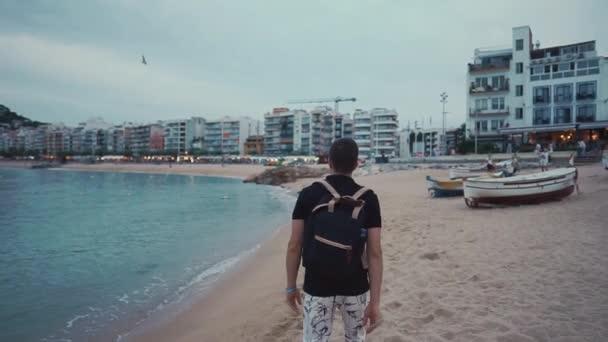 schlanker Mann läuft abends über Strand einer kleinen Kurstadt, Rückansicht