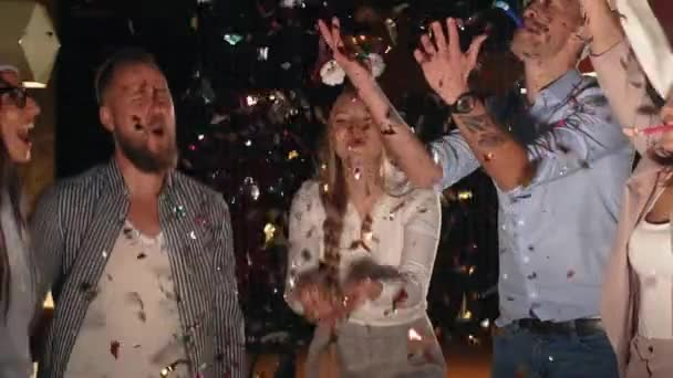 Happy young people are having fun in Christmas night, tossing confetti