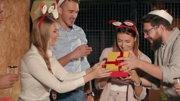 Happy woman is opening a gift on Christmas party and rejoicing, thanking friends
