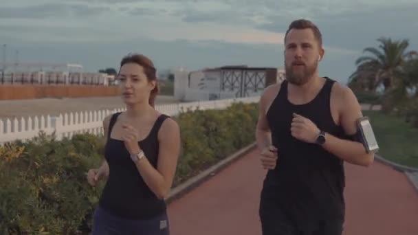 Radostný mužský a ženský běžci se v dopolední době pohybují po městském nábřeží.