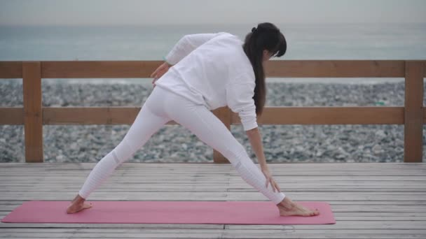 Brunette woman is doing yoga asanas outdoors in seashore in daytime