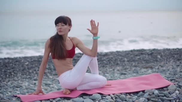 Sportlerin macht Atemübungen in Yoga-Asana am Meeresufer