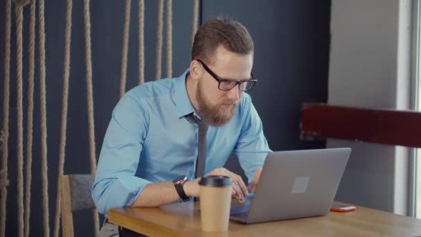 Veselý muž se dívá na obrazovku poznámkového bloku a odpovídá na mobilní hovor