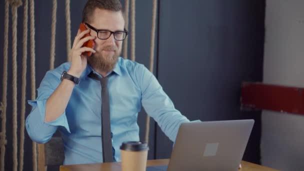 Selbstbewusster Mann telefoniert am Arbeitsplatz im Büro und lächelt
