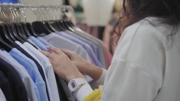 Žena se dotýká košil s tričky v showroom, zblízka na ruce