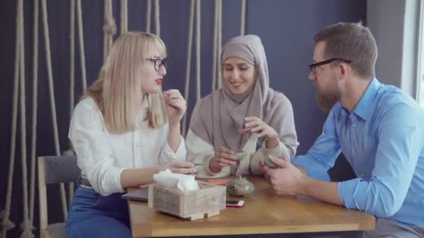 Három kaukázusi és muzulmán barátok férfi és a nők beszélnek, és teát iszik