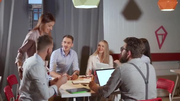 Young creative people are discussing in office space, smiling and laughing