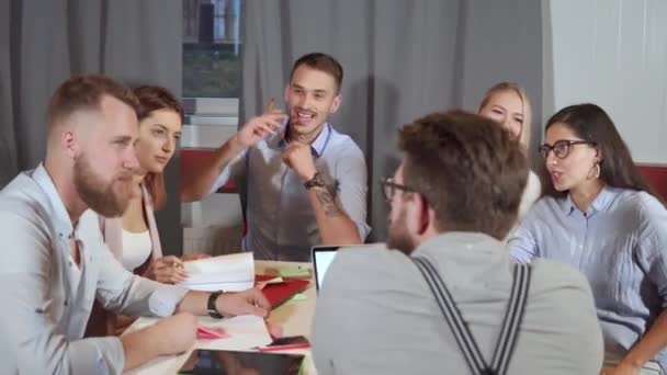 Group of co-workers is meeting in office, chatting cheerfully