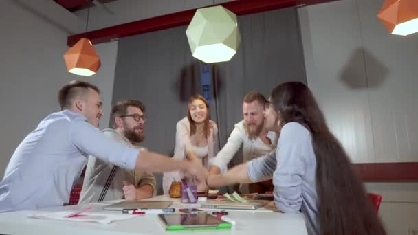 Business team of young people are folding hands together and screaming in office