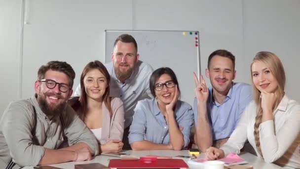 Happy working collective of company is smiling and looking at camera