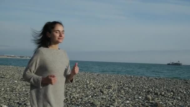 Female runner is training on sea shore in sunny morning, turning to camera