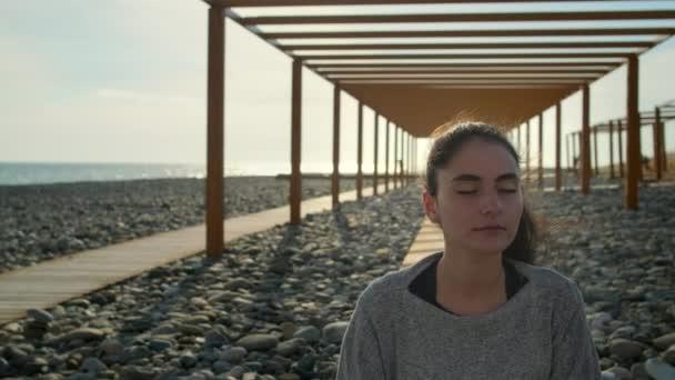Boldog nő pihentető és meditál a tengeri strandon, napsütéses időben