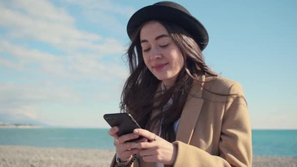 Porträt der jungen Brünetten verschickt Nachrichten per Smartphone im Uferbereich