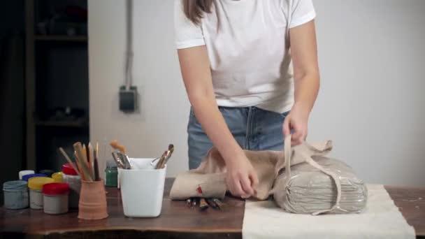 Frau zieht in ihrer Bastelwerkstatt Schürze an und steht neben Tisch,