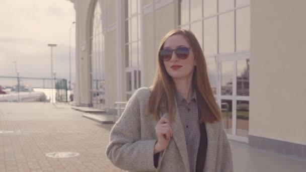 Mosolygó fiatal nő sétál utcai város napos tavaszi napon
