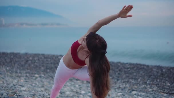 Brunette woman doing yoga outdoor on the beach.