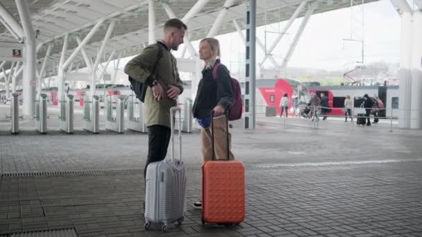 Šťastný pár cestujících stojící na nástupišti s kufry před odjezdem