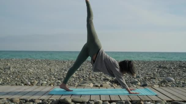 Girl practicing yoga on beach shore alone.