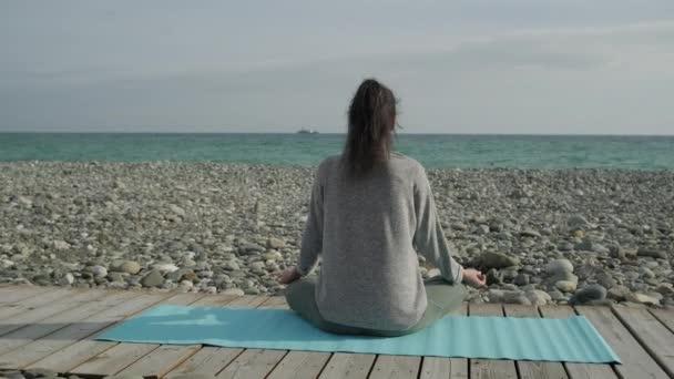 Bruneta, Žena meditující na pobřeží.