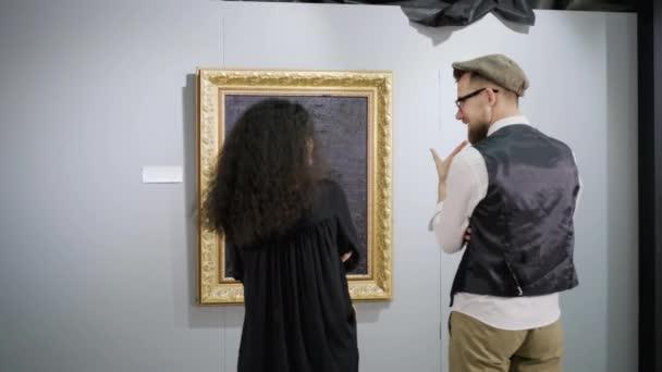 Zwei Besucher der Ausstellung der modernen Kunst plaudert vor Bildern