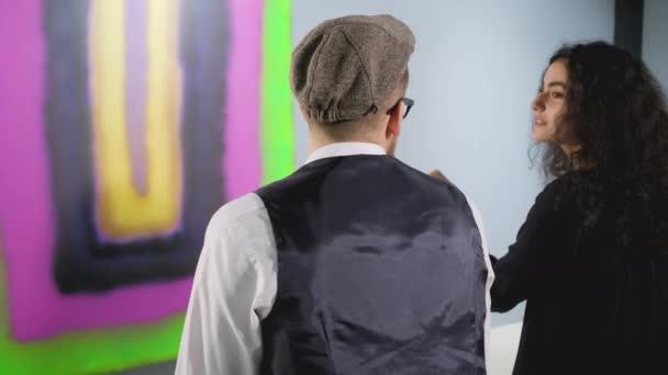 Zwei Besucher des Museums für moderne Kunst sitzen auf der Bank vor dem abstrakten Bild