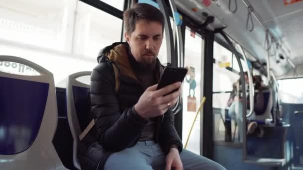 Člověk jede autobusem a dívá se na obrazovku smartphone