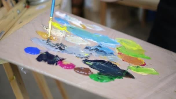 Umělec míchací barvy na dřevěné paletě v dílně, pohled zblízka