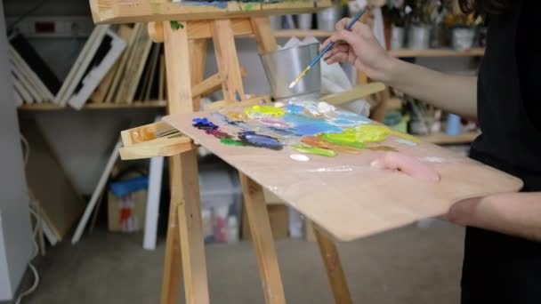 Ženská umělkyně dělá světle modrou barvu na paletě, míchací barviva, zblízka