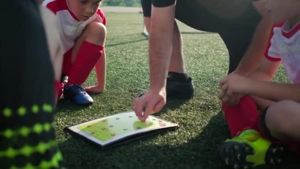 coach explains game tactic moving figures on scheme