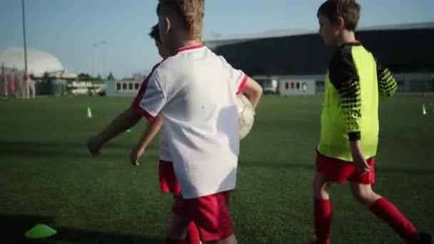 Kluci fotbalisté chodí po hřišti na stadionu