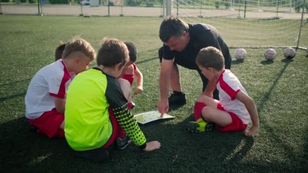Trenér zobrazuje plán fotbalového hřiště pro malé chlapce fotbalistů