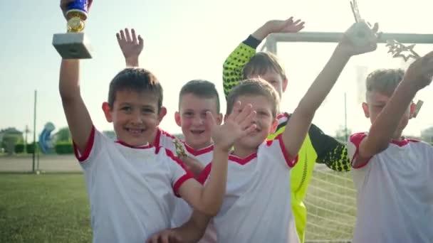 fotbaloví hráči mávnutím ruky za trofej branou