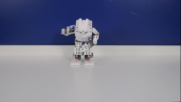 Malá zábavná robotka luky a ruce tančí tanec