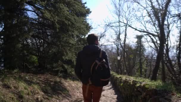 turista v bundě putuje podél starobylé skalnaté stezky