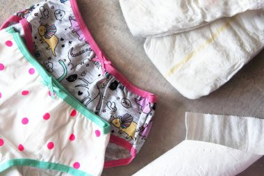 Toddler training on the pot, colorul panties and diapers.