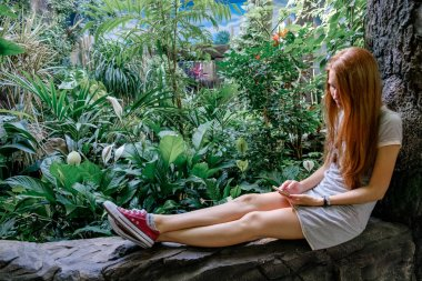 Smilling woman sitting in a tropical park and making a photo on a smartphone. A tourist on an excursion to the zoo.