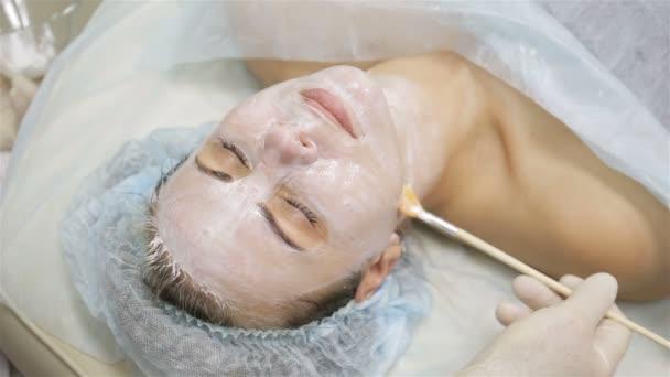 Frau bekommt Gesichtspeeling-Maske im Wellness-Schönheitssalon von Kosmetikerin