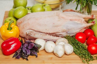 Raw stuffed goose with apples, mushrooms, herbs and vegetables on wooden board