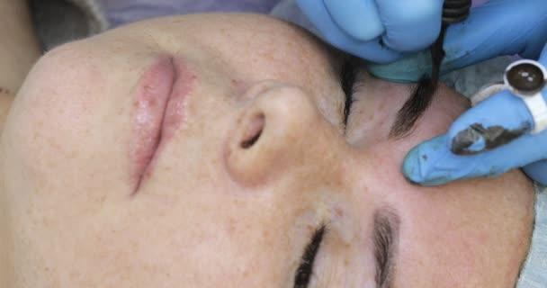 Trucco permanente, tatuaggio delle sopracciglia. Cosmetologo applicazione compongono con macchina per donna nel salone di bellezza