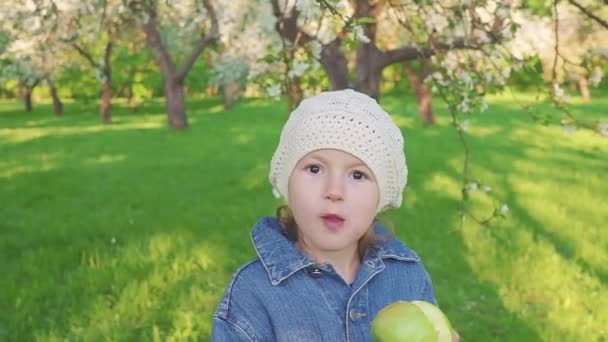 Little girl portrait eating green apple outdoor. A girl with an apple on the background of flowering gardens.