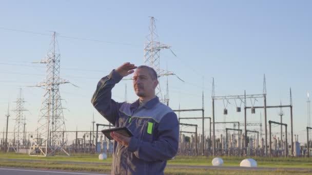 Inženýr a pracovník na elektrické rozvodny. Pracovník s tabletem a schránky ve schůzi v elektrické rozvodny